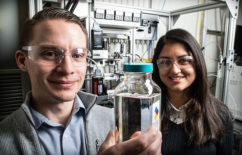 Derek Vardon and Nabila Huq display a container of high-performance ether diesel bioblendstock manufactured at NREL. Credit: Dennis Schroeder/NREL